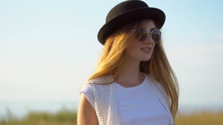 Young beautiful woman model in hat and sunglasses posing outdoor