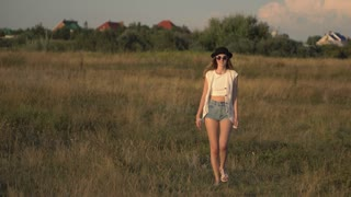 Young beautiful woman model walking on the meadow and enjoying the nature