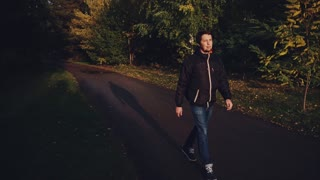 Young calm man in black jacket walking in the autumn park dramatic light