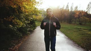 Young calm man in black jacket walking in the autumn park