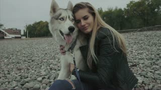 Young cute woman with siberian husky dog sitting on the coast