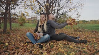 Young happy couple playing and throwing leaves in the autumn park