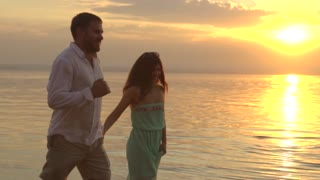 Young happy couple running on the beach on the sunset. Concept of love.