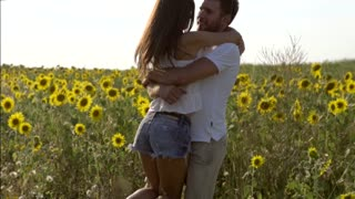 Young man embracing and spinning his girlfriend in field concept of happy couple