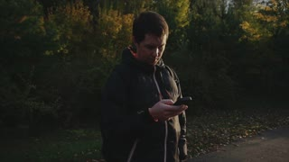 Young man in black jacket in the autumn park surf the internet using smartphone