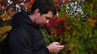 Young man in black jacket in the autumn park using his smartphone