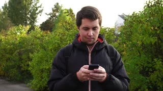 Young man in black jacket surf the internet using his smartphone outdoor