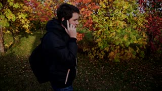 Young man in black jacket walking in the autumn park talking on the phone