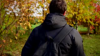 Young man in black jacket walking in the autumn park using his smartphone