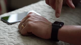Young man using his smart watch app close up hands