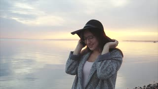 Young pretty and smiling woman in black hat and glasses near the sea at sunset