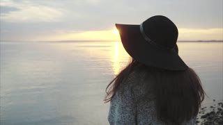 Young pretty smiling woman in black hat and glasses near the sea at sunset