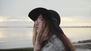 Young pretty smiling woman in black hat and glasses sitting near sea at sunset
