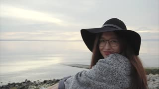 Young pretty smiling woman in black hat and glasses sitting near the sea sunset