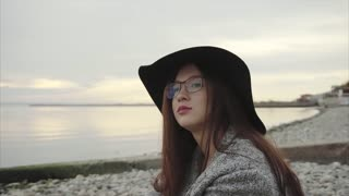 Young pretty wistful woman in black hat and glasses sitting near the sea sunset