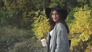 Young pretty woman in black hat and glasses drinking coffee outdoor