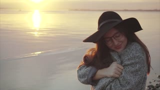 Young pretty woman in black hat and glasses near the sea at sunset