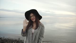 Young pretty woman in black hat and glasses showing thumb up near sea at sunset