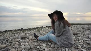 Young pretty woman in black hat and glasses sitting near the sea at sunset
