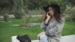 Young pretty woman in black hat and glasses talking on phone outdoors in a park