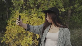 Young pretty woman in black hat and glasses using her smartphone to make selfie