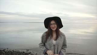Young pretty woman in black hat and glasses waving a hand near the sea at sunset