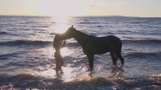 Young sexy woman dressed bikini rest with horse in the river water sunset
