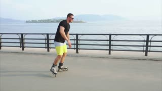 Young sporty man learns to roller skate and jump on waterfront