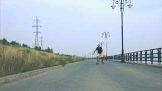Young sporty man with inline skates ride and jump in summer waterfront