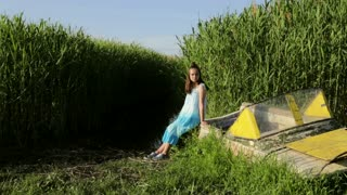 Young teenage girl sitting on old boat near lake rural green reeds background