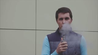 Young vaper man exhaling big clouds of smoke with e-cigarette vape slow motion