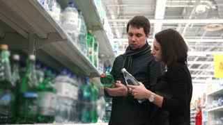 Young woman and her husband choose mineral water.