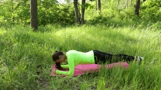 Young woman doing plank exercise on mat in park look at camera smiling