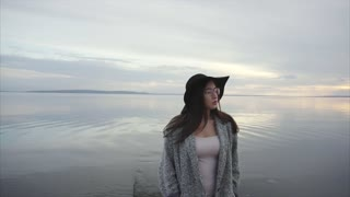 Young woman in black hat and glasses looking around sea coast at sunset