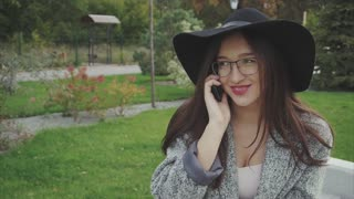 Young woman in black hat and glasses talking on phone sits on the bench in park