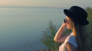 Young woman in sunglasses sit on the edge of a cliff enjoying the nature
