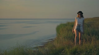 Young woman in walk dance and jump on the edge of a cliff enjoying the nature