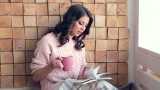 Young woman reading book at home and drinking coffee