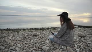 Young woman sitting on pebble beach throwing stones into the water