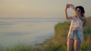 Young woman uses a smartphone to shot video a beautiful sunset view