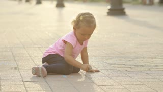A little girl drawing on pavement with chalk