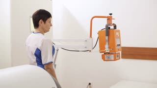 A woman setting up x-ray machine in clinic