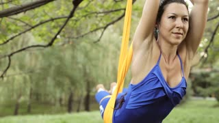 Anti-gravity Yoga, woman doing yoga exercises with hammock in the park