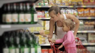 Attractive young woman with baby daughter selecting a drinks in supermarket.