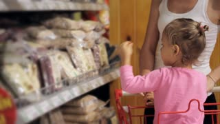Attractive young woman with baby daughter shopping in supermarket.