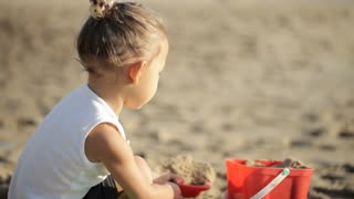 Baby girl playing with red toy bucket and shovel on the sandy beach