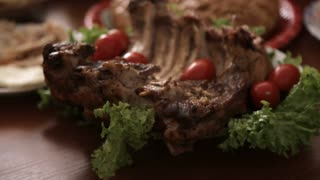 Banquet table with big piece of grilled meat with tomatoes and lettuce