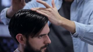 Barber combing the hair of the client before haircut at a barber shop