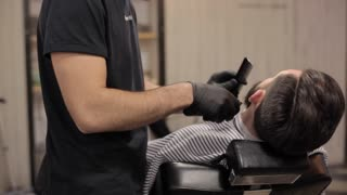 Barber cutting beard with electric razor at a barber shop.