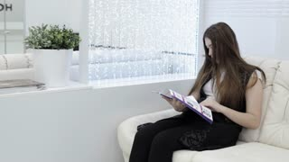 Beatiful girl looking magazine at hole of dental clinic